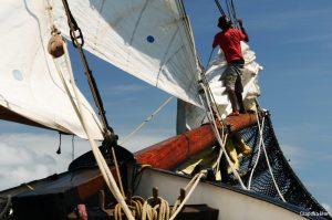 Seychelles 35 metre traditional schooner hoisting foresail standing on Bow Spreader